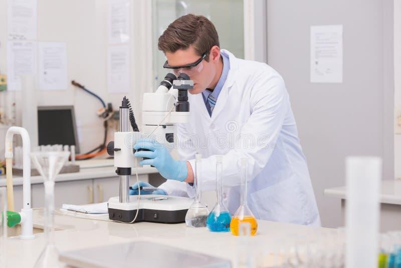 Científico que mira a través de un microscopio fotografía de archivo libre de regalías