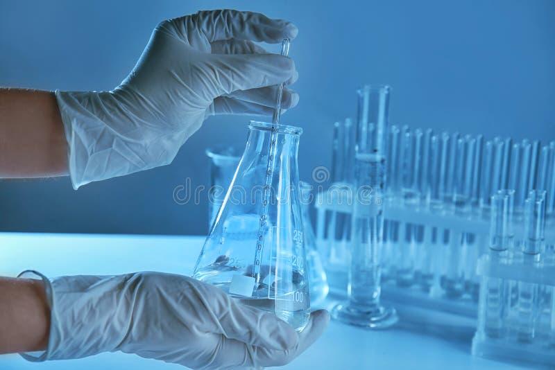 Científico que sostiene el frasco cónico con el líquido y la pipeta en laboratorio foto de archivo