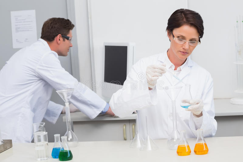 Científico que vierte el líquido químico en embudo y a su colega que trabaja con el ordenador imagen de archivo libre de regalías