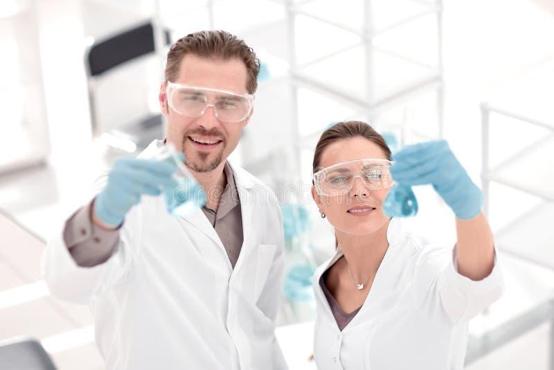 Científico y ayudante con los tubos, colocándose en el laboratorio fotos de archivo