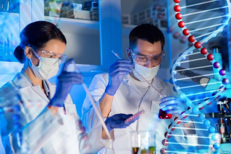 Científicos con las pipetas y los tubos de ensayo en laboratorio fotos de archivo