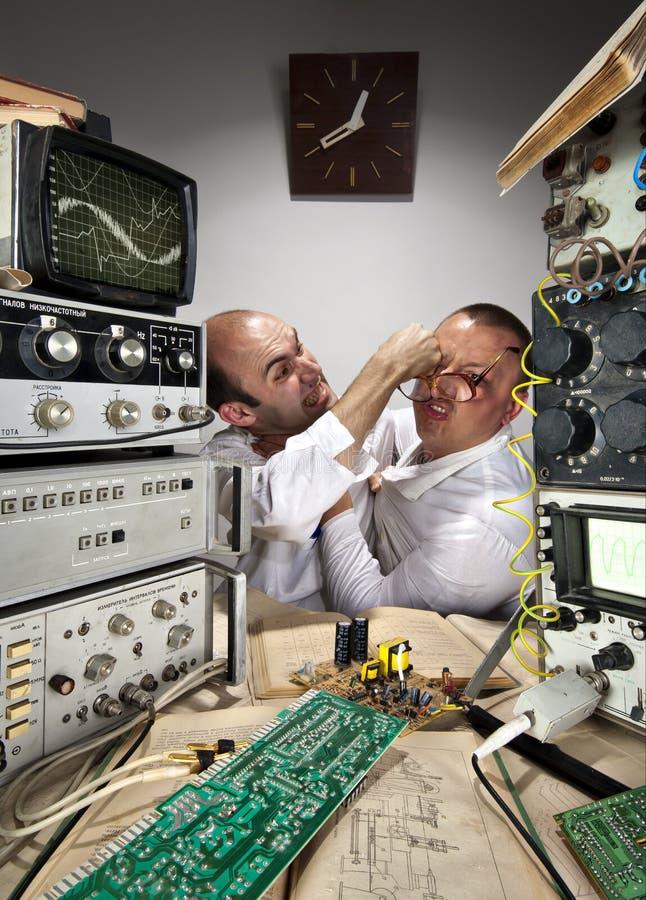 Científicos divertidos del Wo que luchan en el laboratorio foto de archivo