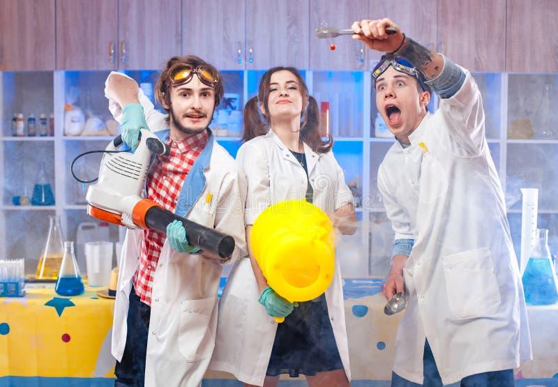 Científicos jovenes divertidos en laboratorio junto fotos de archivo
