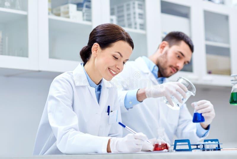 Científicos jovenes que hacen la prueba o la investigación en laboratorio fotos de archivo