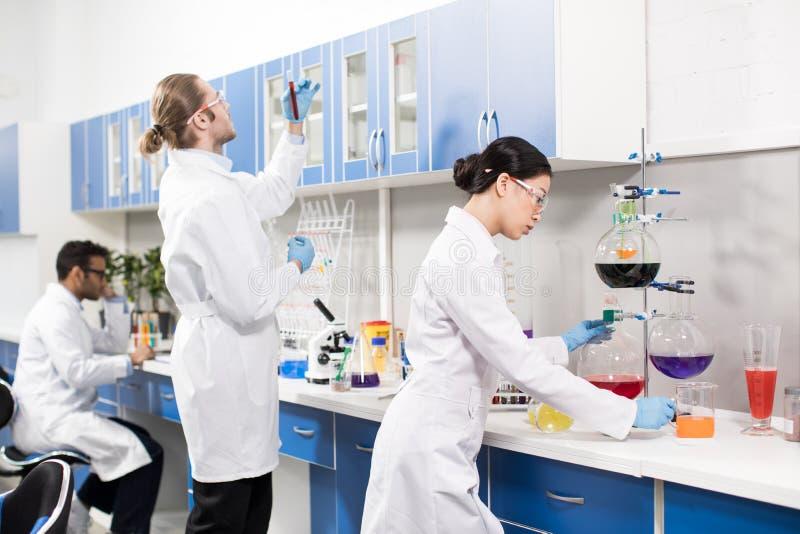 Científicos profesionales jovenes que hacen el experimento en laboratorio de investigación fotografía de archivo