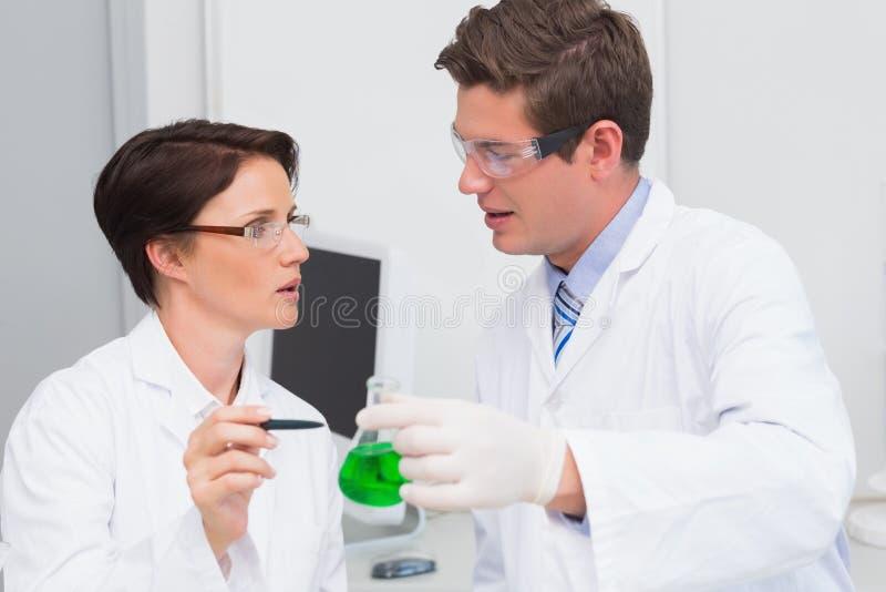Científicos que examinan atento el cubilete con el líquido verde imagen de archivo