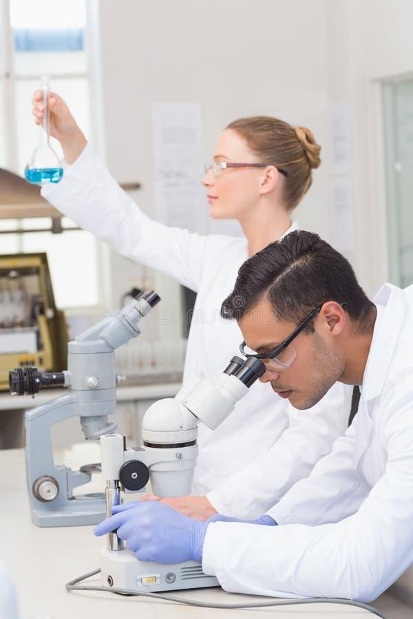 Científicos que examinan el precipitado azul imagenes de archivo