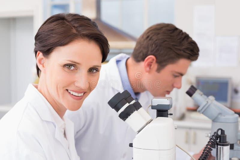 Científicos que miran atento en microscopios fotos de archivo libres de regalías
