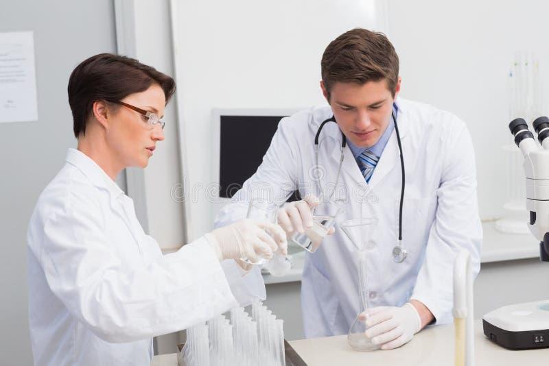 Científicos que vierten el líquido químico en embudo foto de archivo