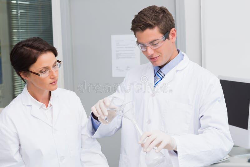 Científicos que vierten el líquido químico en embudo fotos de archivo