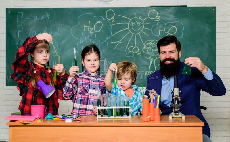 Cient?ficos en el trabajo estudiantes que hacen experimentos de la ciencia con el microscopio en laboratorio De nuevo a escuela e imagen de archivo