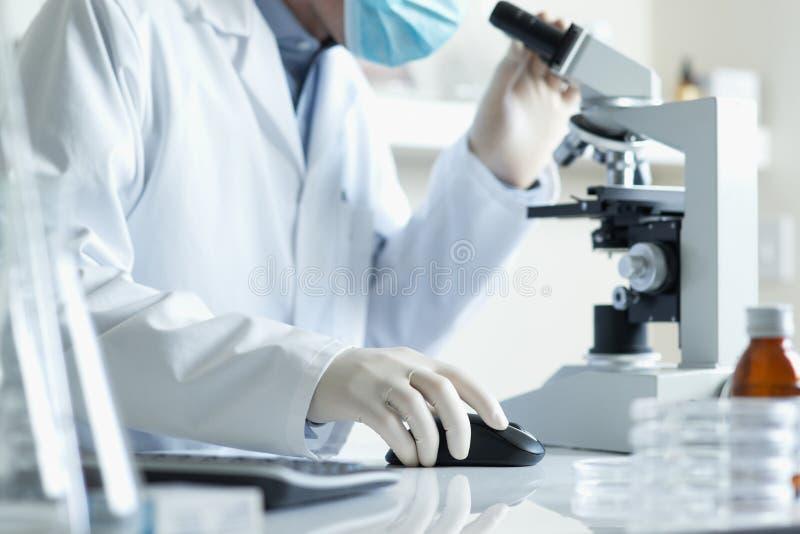 Cientista com computador do microscopeand fotos de stock royalty free