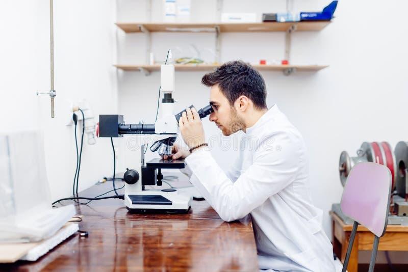 Cientista com microscópio, as amostras de exame e pontas de prova contaminadas no laboratório especial fotografia de stock royalty free
