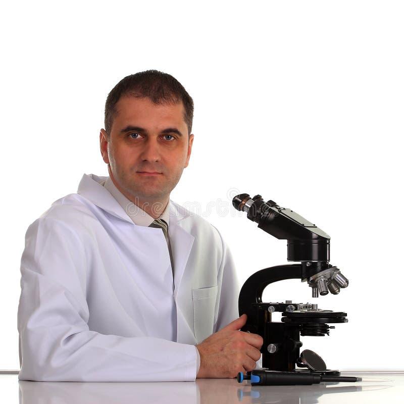 Cientista com o microscópio isolado no branco imagens de stock