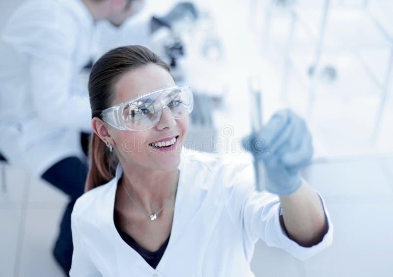 Cientista das mulheres com o tubo de ensaio que faz a pesquisa no laboratório clínico fotografia de stock