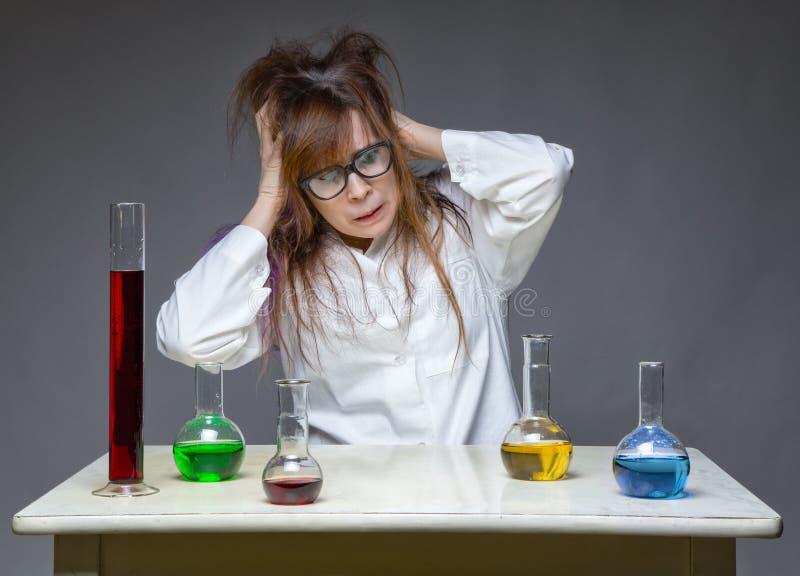 Cientista desarrumado principal de agarramento no laboratório imagem de stock
