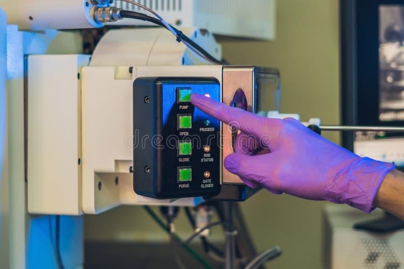 Cientista em trabalhos de laboratório com uma porta do microscópio de elétron imagem de stock