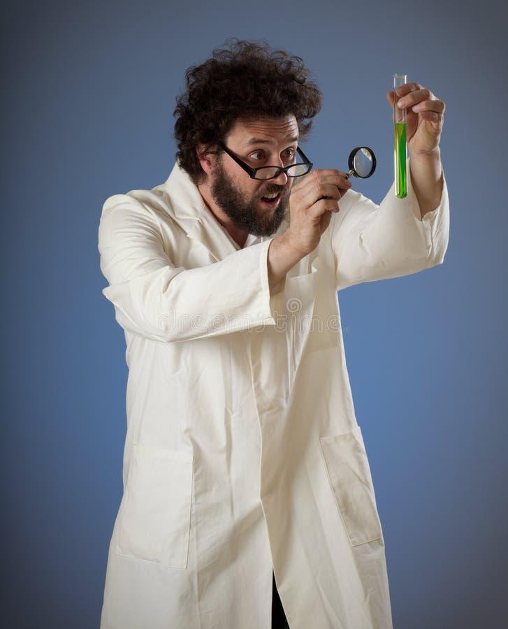 Cientista estranho que styudying o líquido verde imagens de stock