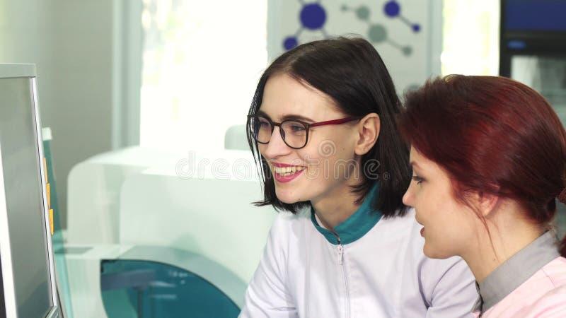 Cientista fêmea bonito que fala a seu colega imagem de stock