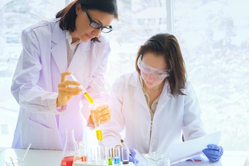Cientista fêmea novo que está com techer na fatura do técnico de laboratório fotos de stock