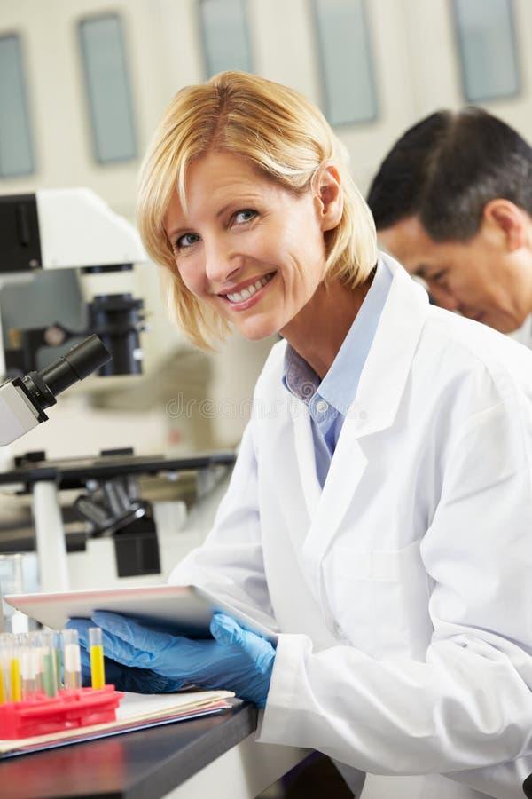 Cientista fêmea que usa o computador da tabuleta no laboratório fotografia de stock