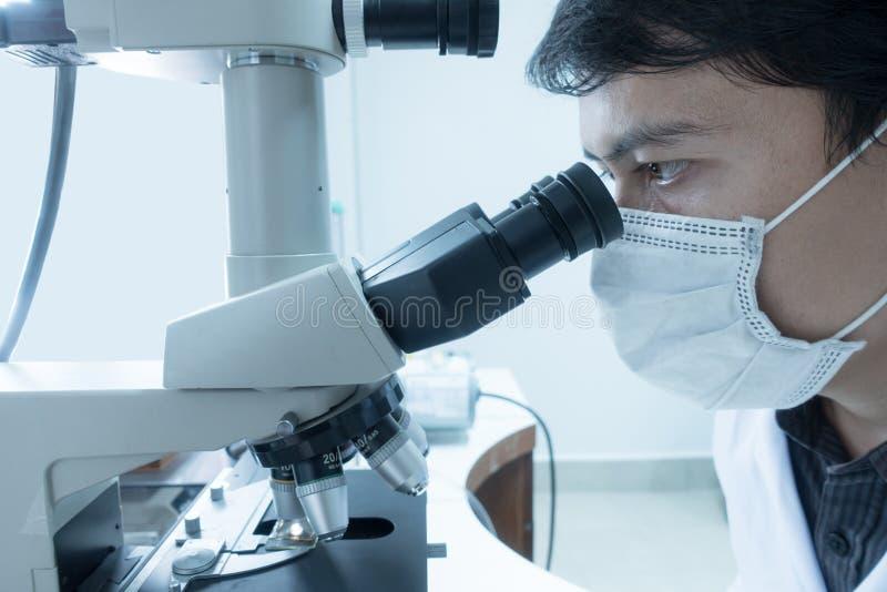 Cientista masculino que faz o microscópio fotografia de stock