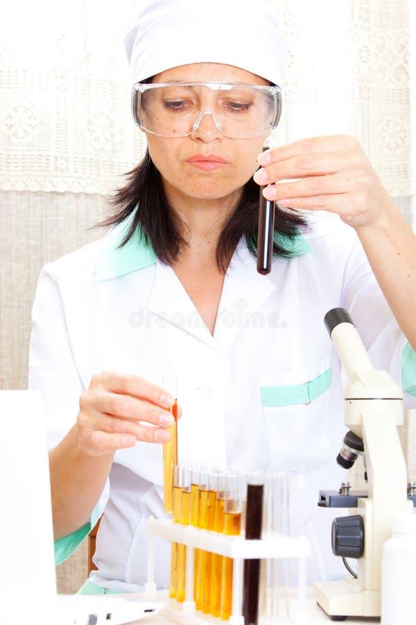 Cientista no laboratório que analisa o líquido amarelo no tubo de ensaio fotos de stock