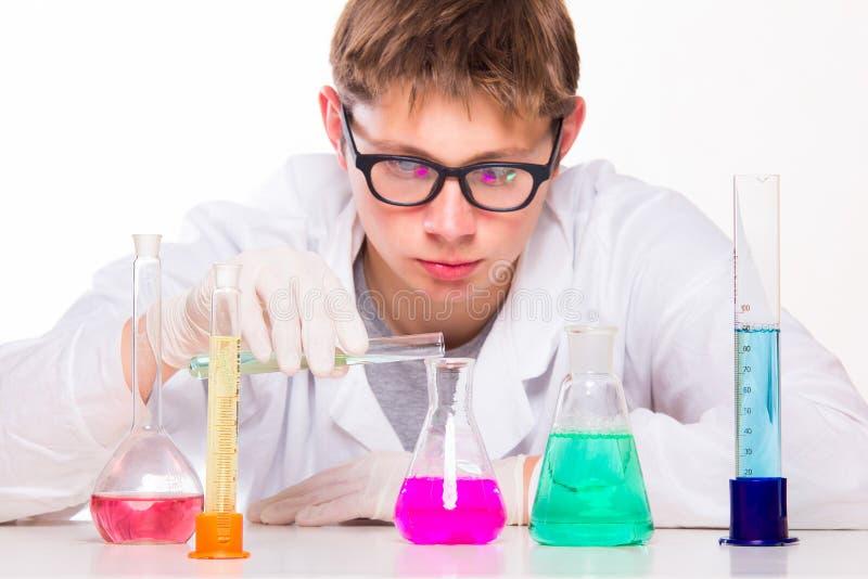 Cientista novo que faz reações químicas no laboratório fotos de stock