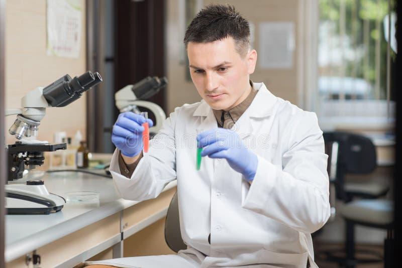 Cientista novo que trabalha com materiais líquidos fotos de stock