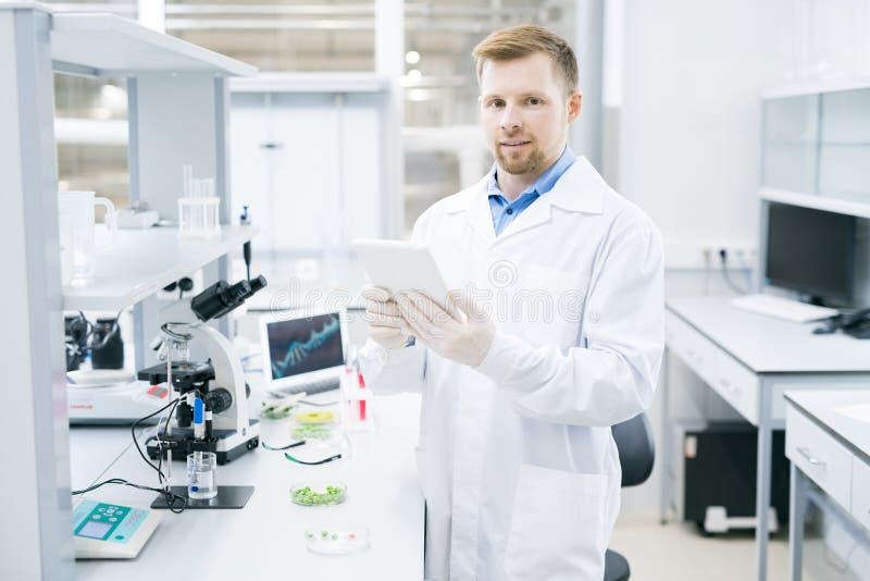 Cientista que está com a tabuleta no laboratório fotos de stock royalty free