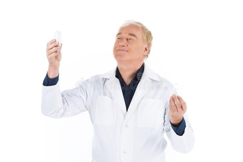 Cientista que guarda duas lâmpadas acima em ambas as mãos imagens de stock