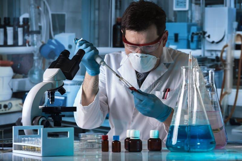 Cientista que introduz com pipeta a amostra de teste do tubo no laborato da pesquisa fotografia de stock