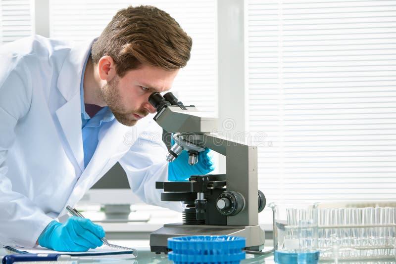 Cientista que olha através de um microscópio foto de stock