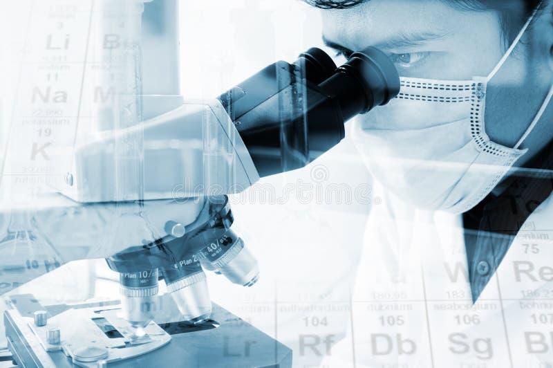 Cientista que olha através de um microscópio para a amostra do teste da química fotografia de stock royalty free