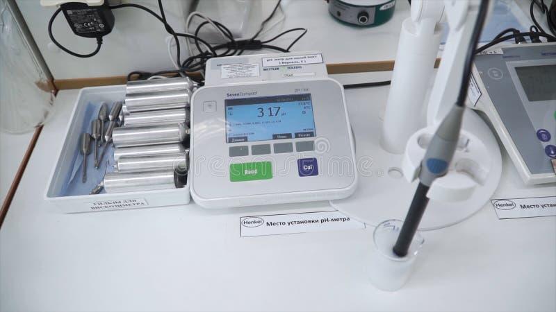 Cientista que usa luvas protetoras para segurar substâncias perigosas e experiências grampo Testes da substância dentro fotografia de stock royalty free