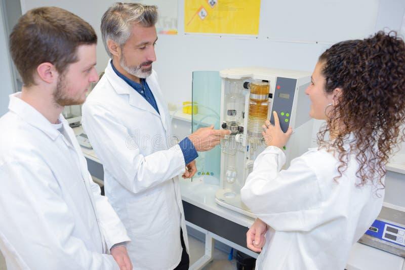 Cientistas alegres do professor e do estudante do retrato que fazem a experiência imagens de stock