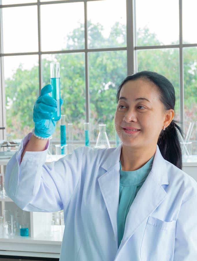 Cientistas asiáticos da mulher da Idade Média Sorrir, está trabalhando o tubo de ensaio para fazer a pesquisa imagem de stock royalty free