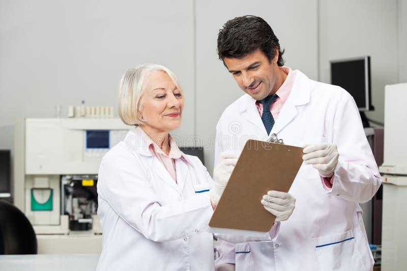 Cientistas que escrevem na prancheta no laboratório imagem de stock royalty free