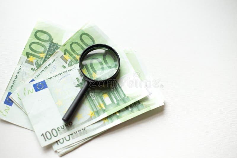 Cientos billetes de banco del euro debajo de la lupa aislada en el fondo blanco fotografía de archivo libre de regalías