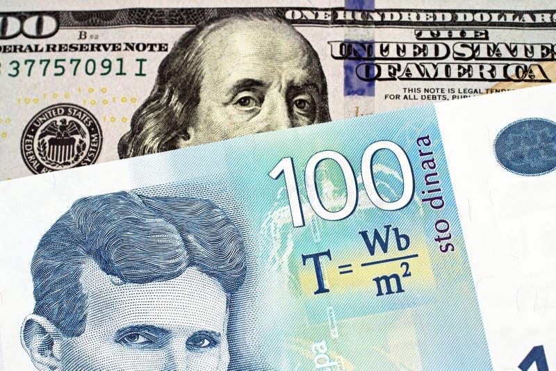 Cientos billetes de banco servios azul del dinar con cientos billetes de dólar americano fotos de archivo