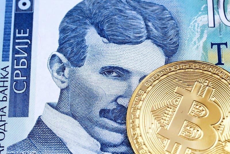 Cientos billetes de banco servios del dinar con un oro Bitcoin físico imágenes de archivo libres de regalías