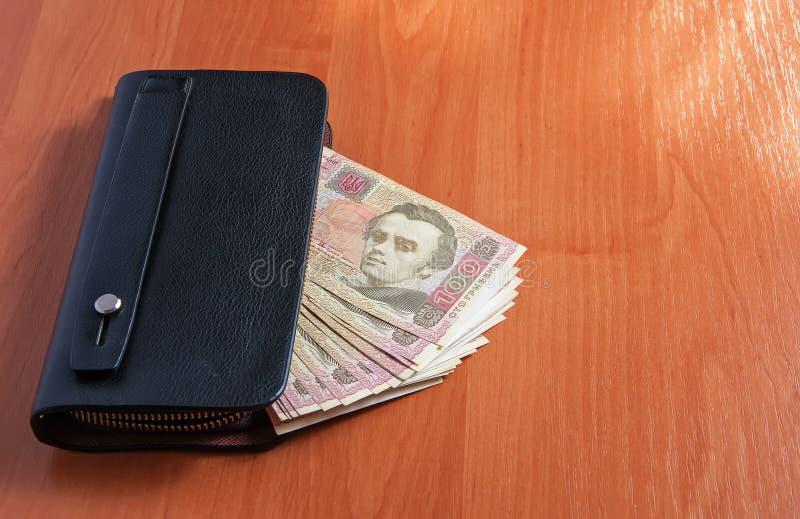 Cientos billetes de banco ucranianos del hryvnia en monedero negro fotos de archivo libres de regalías