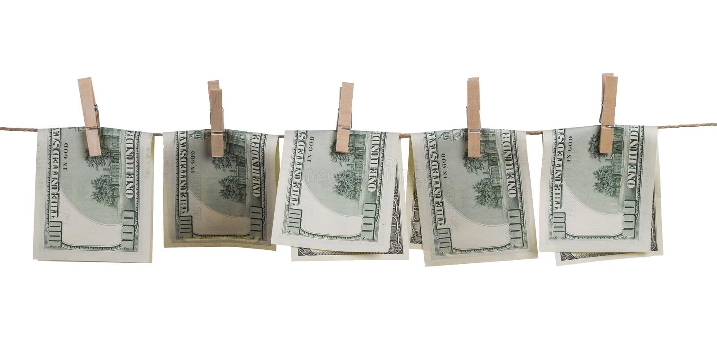 Cientos billetes de dólar doblados por la mitad, atado con las pinzas a una cuerda, aislada en el fondo blanco imagenes de archivo