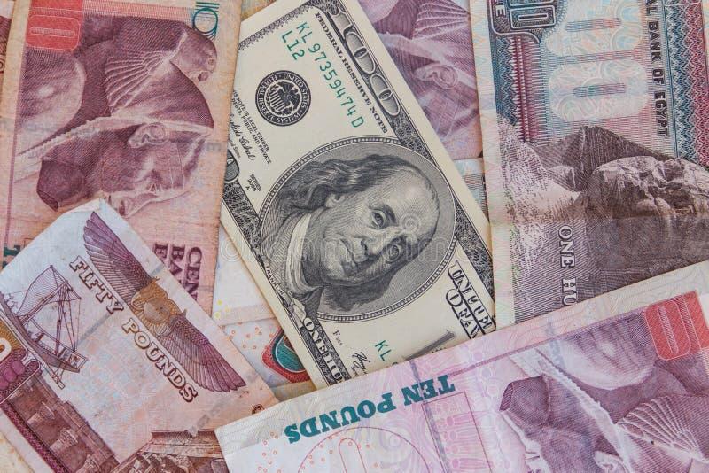 Cientos billetes de dólar en fondo de los billetes de banco de las libras egipcias fotografía de archivo libre de regalías