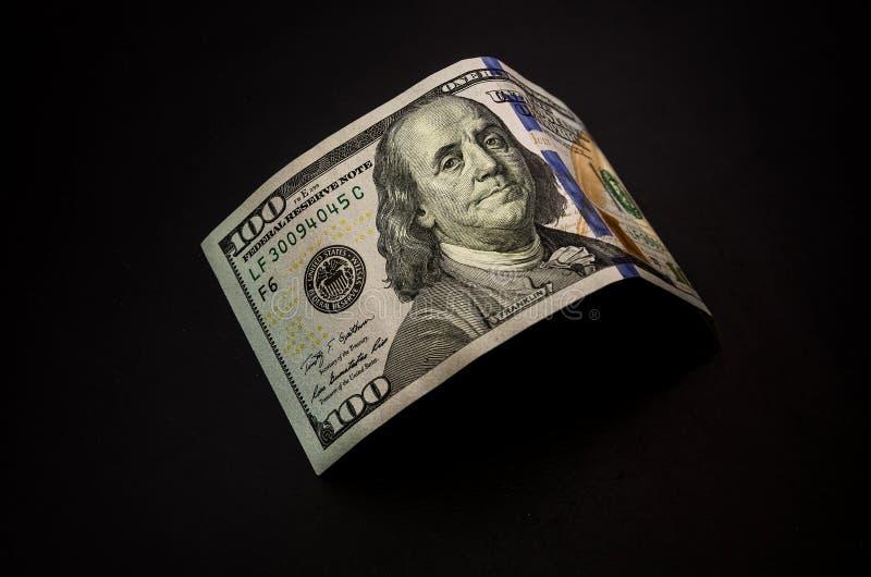 Cientos billetes de dólar en fondo reflexivo negro imagenes de archivo