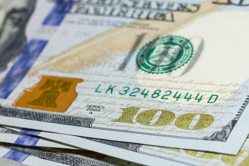 Cientos billetes de dólar se cierran para arriba con el foco selectivo fotos de archivo