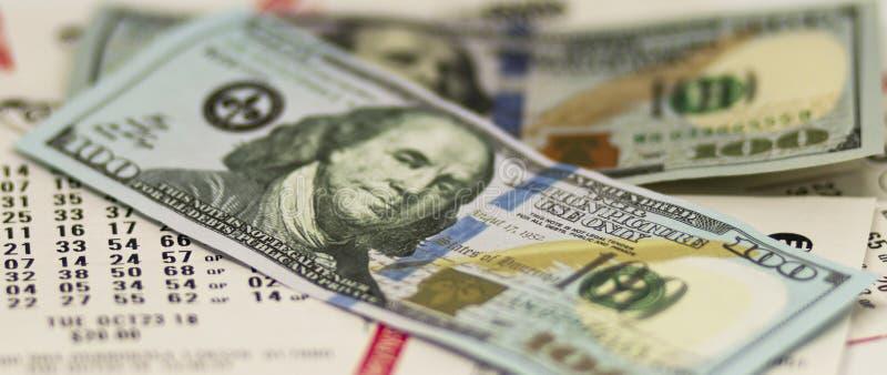 Cientos billetes de dólar sobre boletos de lotería imagen de archivo