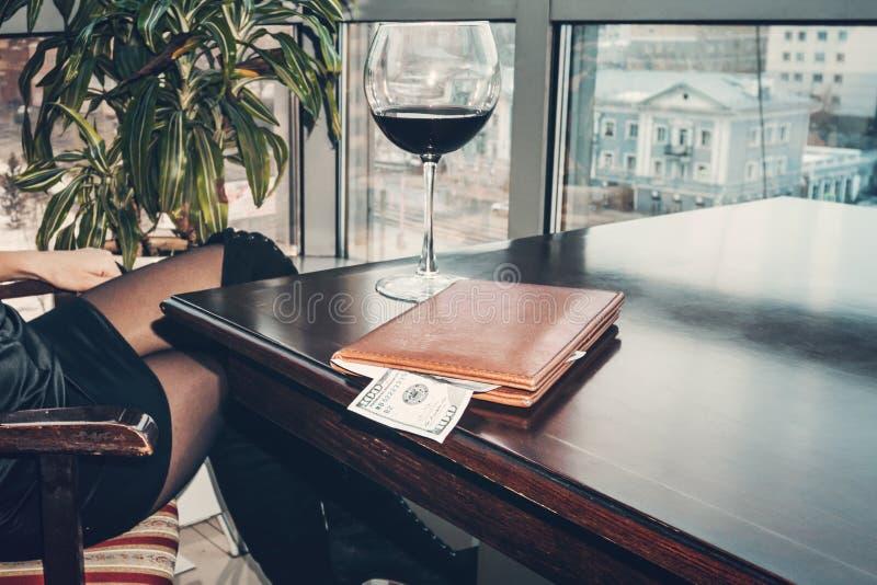 Cientos dólares de extremidad abundante en la tabla en una carpeta de cuero La muchacha bebió el vino y pagó la cuenta Un vino gr imagenes de archivo