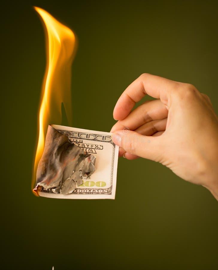 Cientos dólares de quemadura con el fuego en sus manos imagenes de archivo
