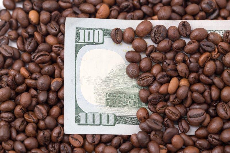 Cientos dólares en granos de café foto de archivo